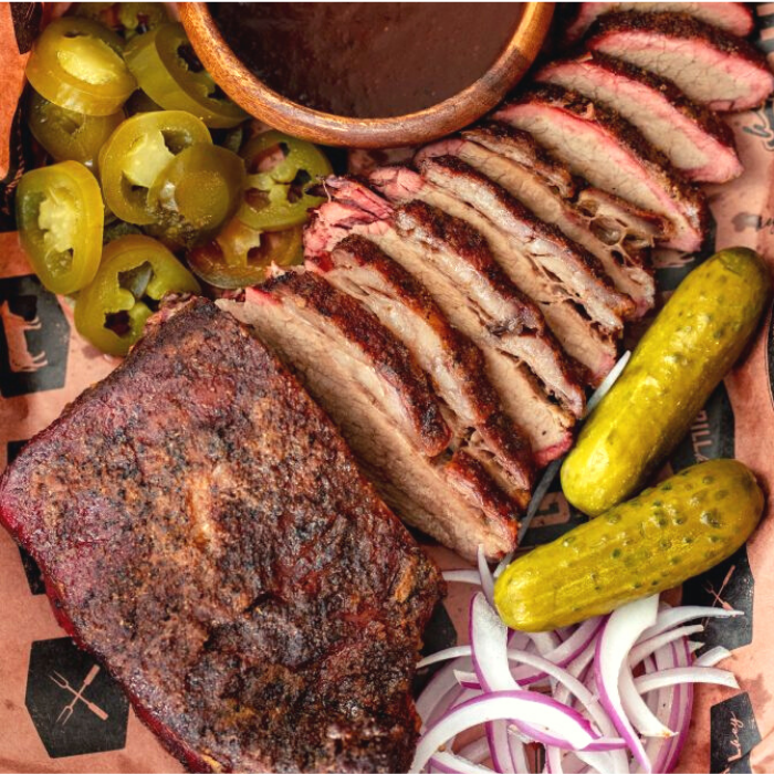 Tri tip cooked like a brisket sliced and arranged on peach butcher paper next to pickles, onions, BBQ sauce, and sliced jalapenos.