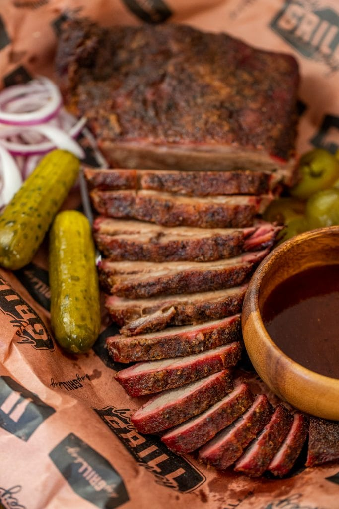 sliced tri tip cooked like a brisket on peach butcher paper surrounded by pickles, jalapenos, onions and BBQ sauce.