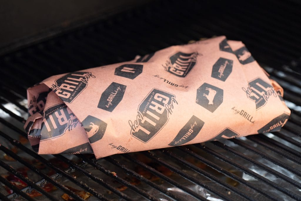 tri tip wrapped in Hey Grill Hey branded peach butcher paper on the smoker
