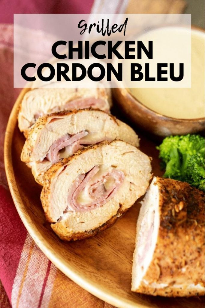 Sliced chicken cordon bleu layered in a wood bowl with a side of broccoli and a bowl of white dipping sauce.