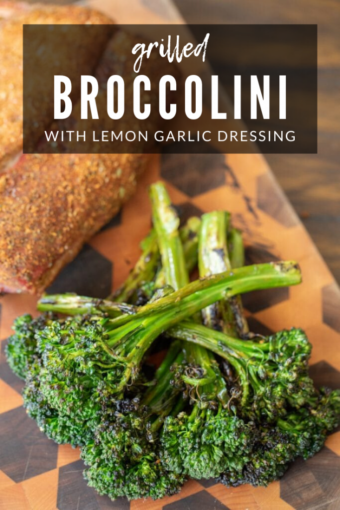 """Stack of grilled broccolini and seasoned meat on a wooden cutting board with text overlay: """"Grilled broccolini with lemon garlic dressing."""""""