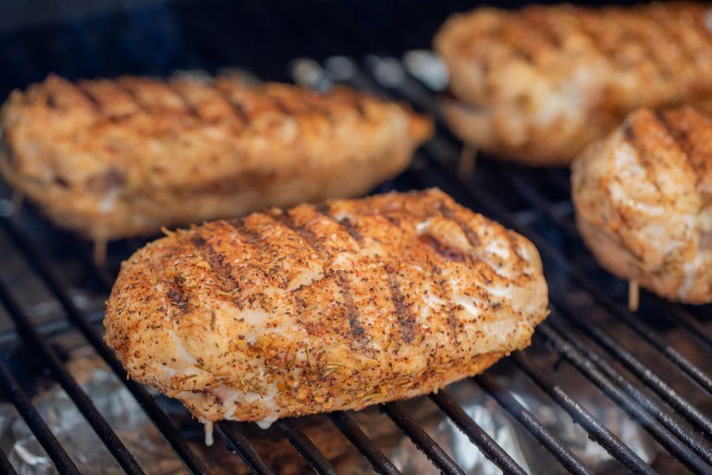 Chicken cordon bleus being grilled on grill grates.