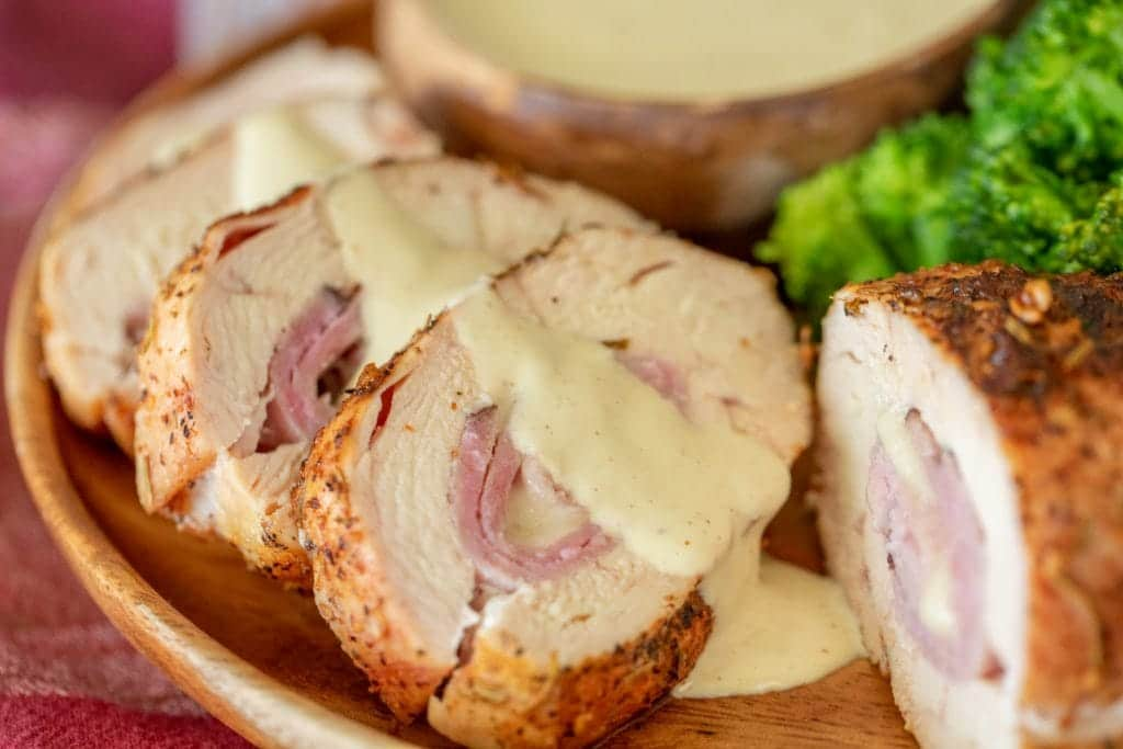sliced chicken cordon bleu lined up in a wooden bowl drizzled with a white dipping sauce.