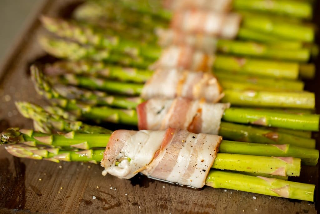 bacon wrapped asparagus bundles on a wooden cutting board