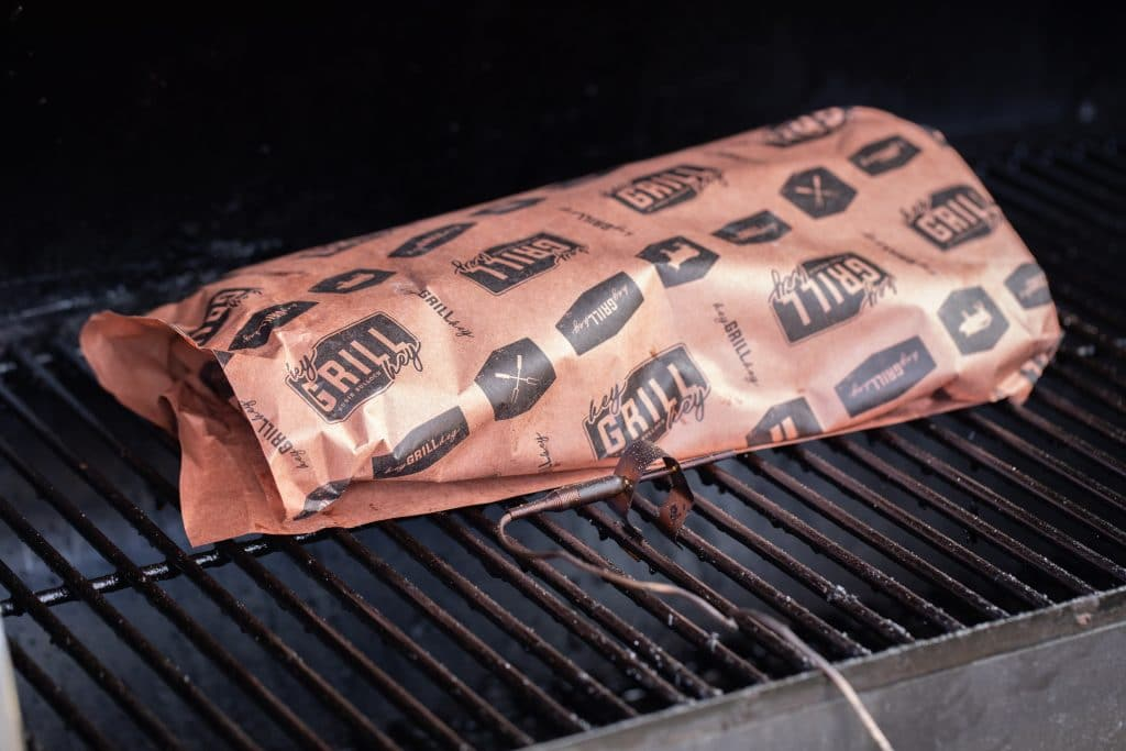 Rack of beef back ribs wrapped in butcher paper on a smoker.