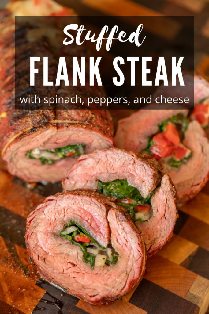 Medium Rare flank steak stuffed with spinach, peppers, and cheese. Four sliced laying in a diagonal to display interior stuffing and arranged on a mixed wood cutting board.