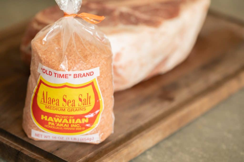 A bag of pink Hawaiian salt on a wood cutting board, with a raw pork shoulder in the background