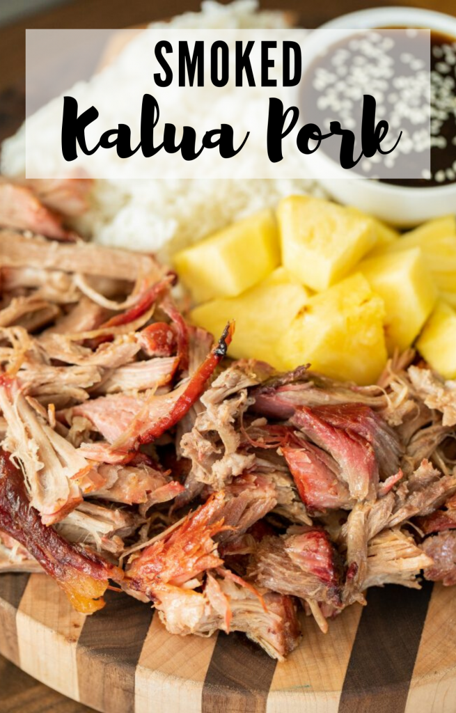 """Vertical image of shredded smoked kalua pork arranged on a wood cutting board with pineapple chunks, rice, and a bowl of teriyaki sauce in the background. Decorative text says """"smoked kalua pork"""""""