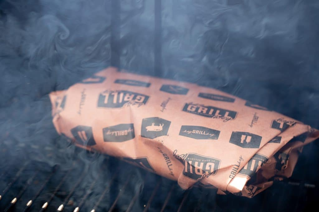 Kalua pork wrapped in pink butcher paper in a smoker