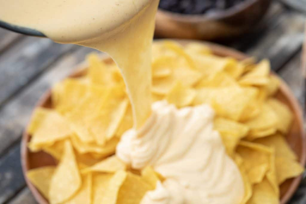 Nacho cheese sauce being poured from a pan onto a pile of tortilla chips.