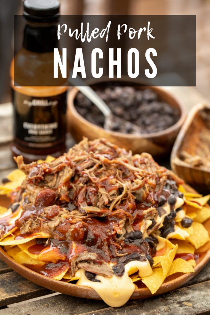 Pulled pork, bbq sauce, black beans, and cheese sauce layered on top of tortilla chips on a wooden plate with bottle of BBQ sauce and bowl of extra black beans in the background with decorative text.