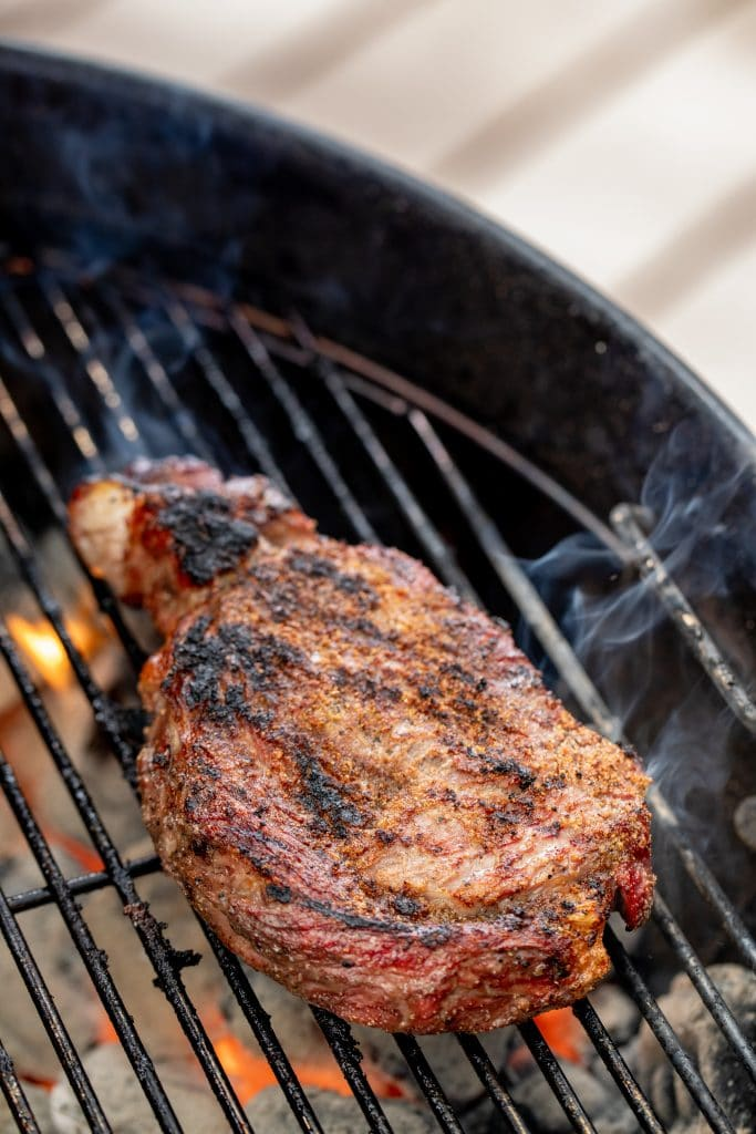 Steak searing on a grill grate over hot coals.
