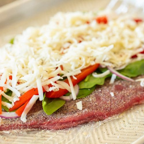 Season and flattened flank steak on a piece of plastic wrap topped with uncooked spinach, roasted bell pepper strips, red onions, and a pile of shredded mozzarella cheese.