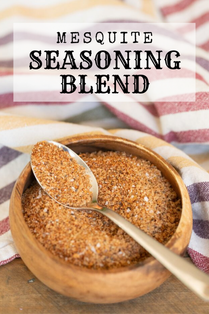 """Metal spoon resting over a wooden bowl full of mesquite seasoning blend with the text overlay: """"Mesquite Seasoning Blend."""""""