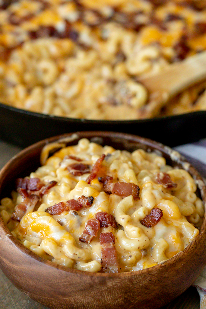 Bacon mac and cheese in a wooden bowl with a skillet of bacon mac and cheese in the background.