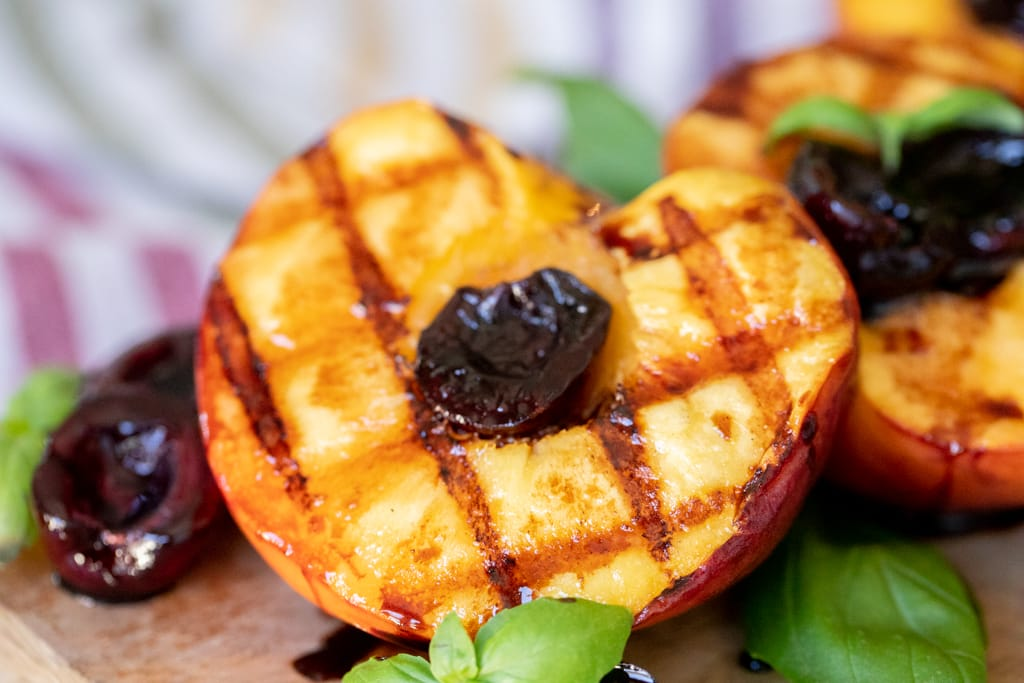 Grilled peaches with grill marks halved and glazed with cherries.