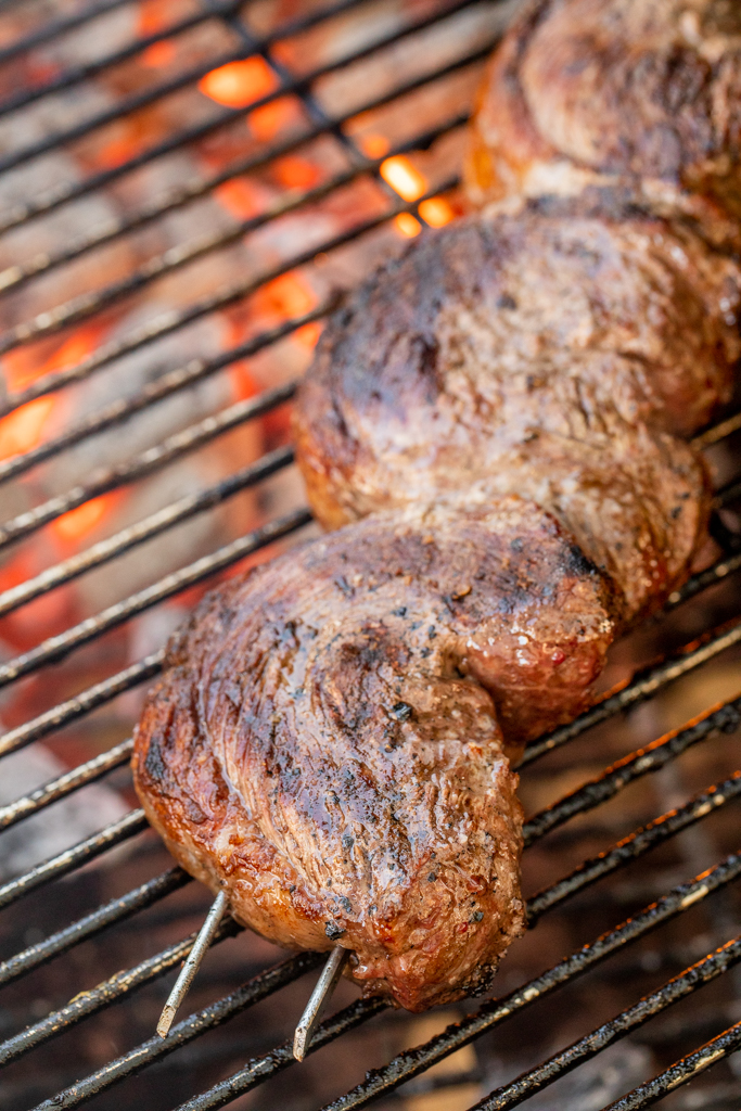Skewered picanha steaks on the grill grates of a charcoal grill.