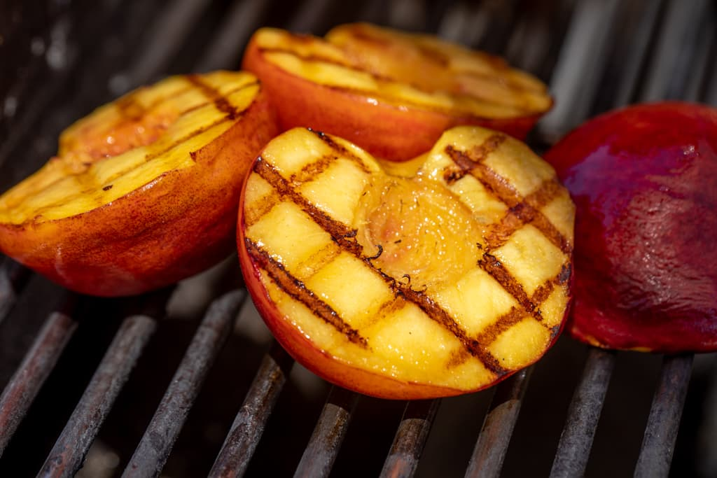 Grilled peaches halved on grill grates.