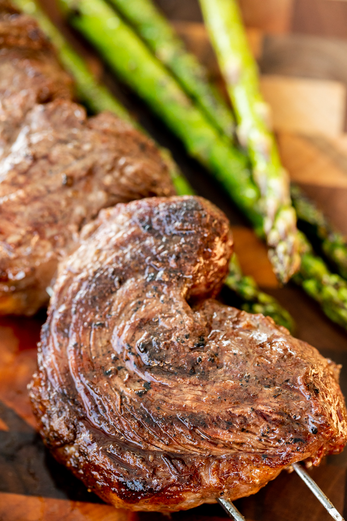 Closeup of a skewered and grilled picanha steak on a wooden cutting board next to grilled asparagus spears.