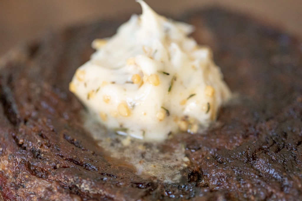 Grilled steak with a dollop of herbed butter resting atop the steak.
