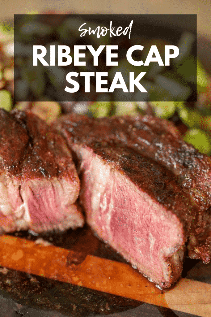 Sliced Ribeye Cap Steak with a portion turned and showing edge to edge medium rare. Grilled brussels sprouts in the background, all on a wood cutting board. Text Overlay: Smoked Ribeye Cap Steak.
