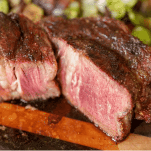 Sliced smoked ribeye cap steak on a wooden cutting board.