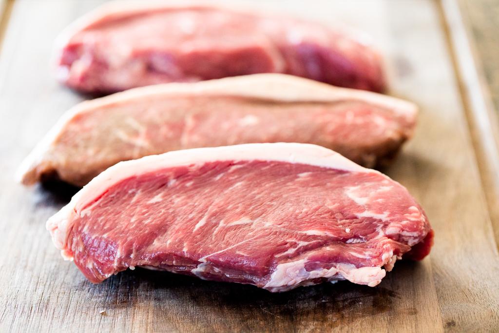 Three raw Picanha steaks on a wooden cutting board.