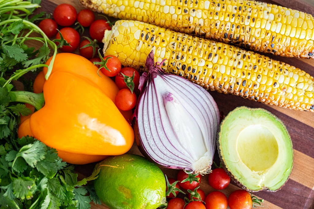 Grilled corn on a wood cutting board with halved avocado, halved red onion, whole lime, whole orange bell pepper, cilantro, and cherry tomoatoes.