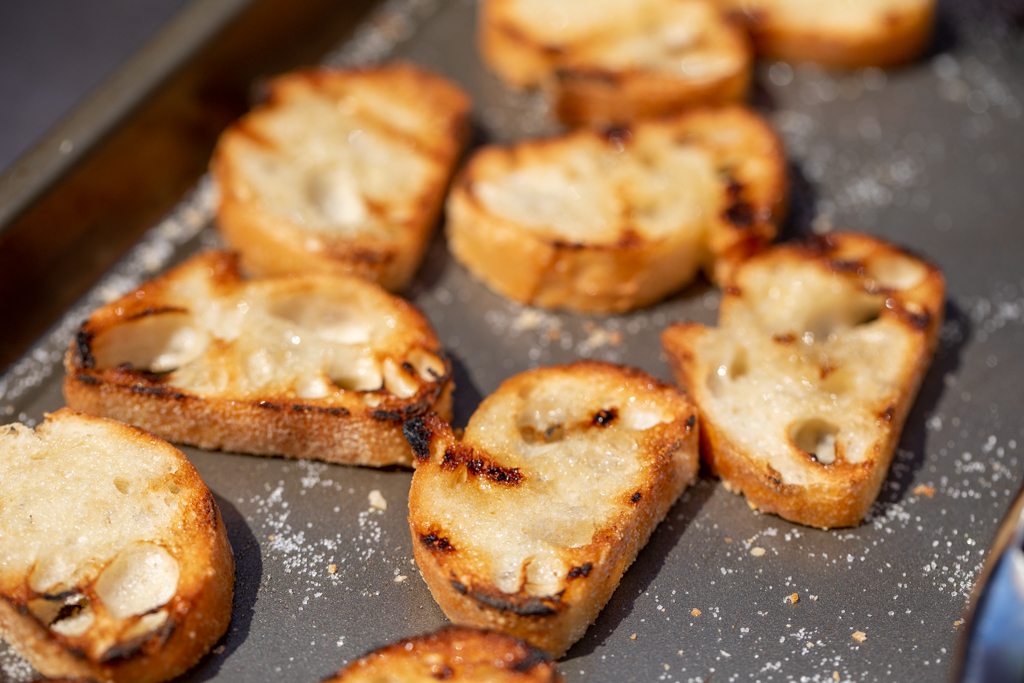 Grilled bread slices on a metal baking sheet.