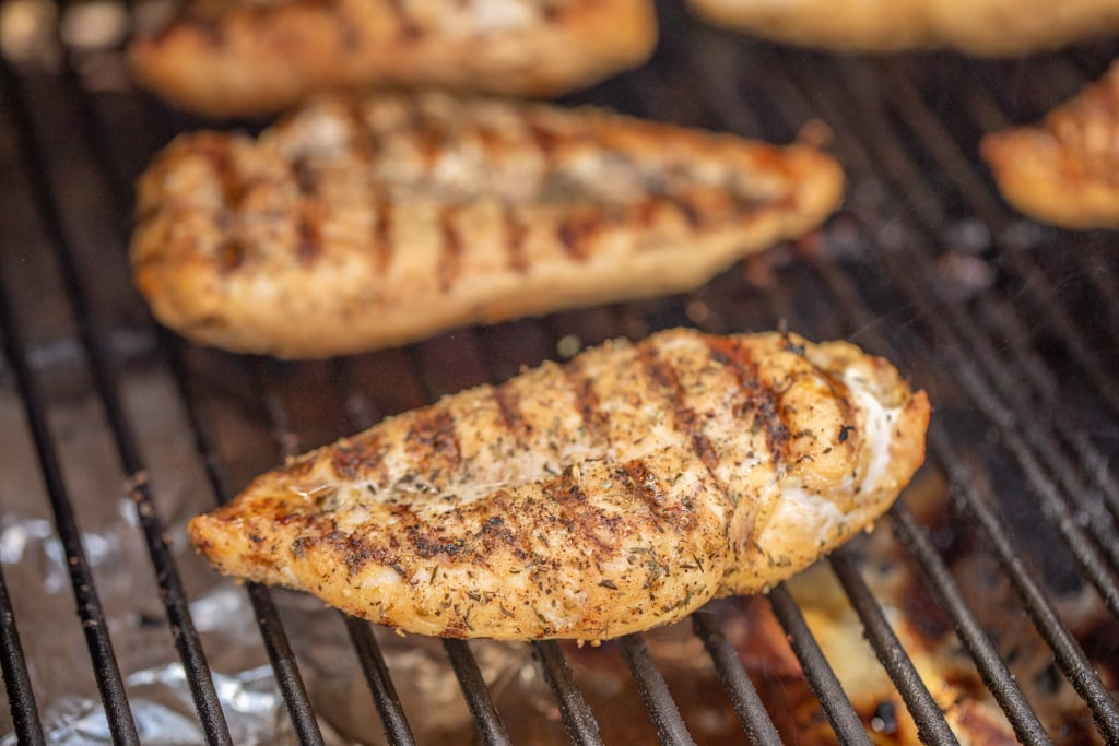 Seasoned chicken breast on grill grates with grill marks.