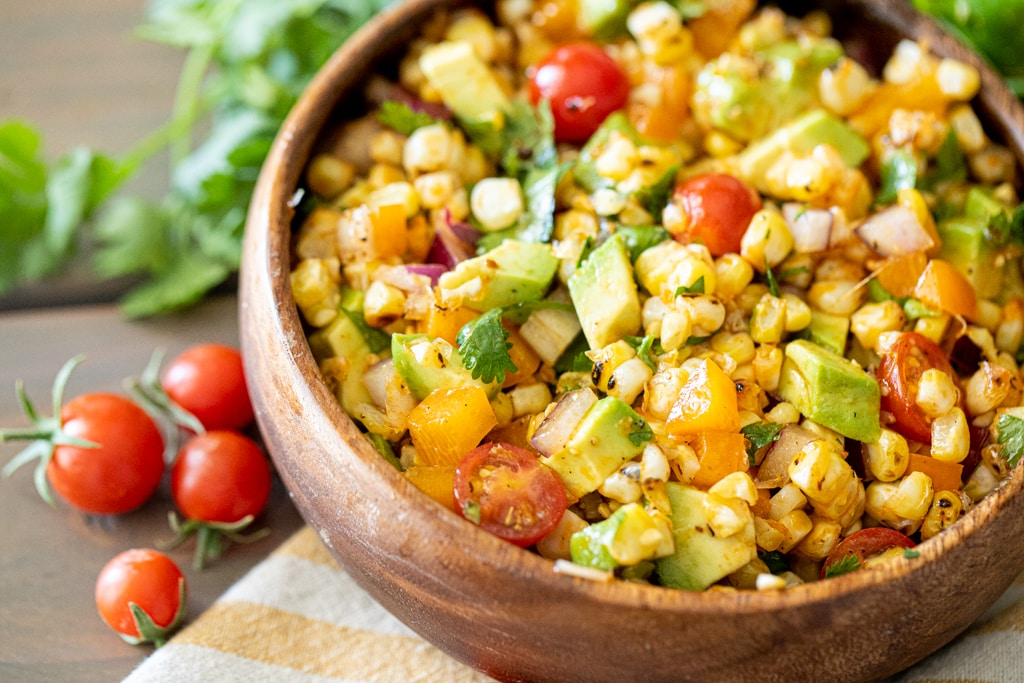 A wooden bowl full of grilled corn salad with cherry tomatoes sitting next to the bowl.
