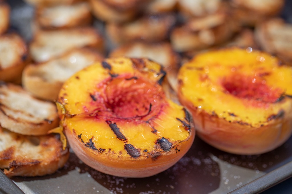 Two grilled peach halves on a metal baking sheet.