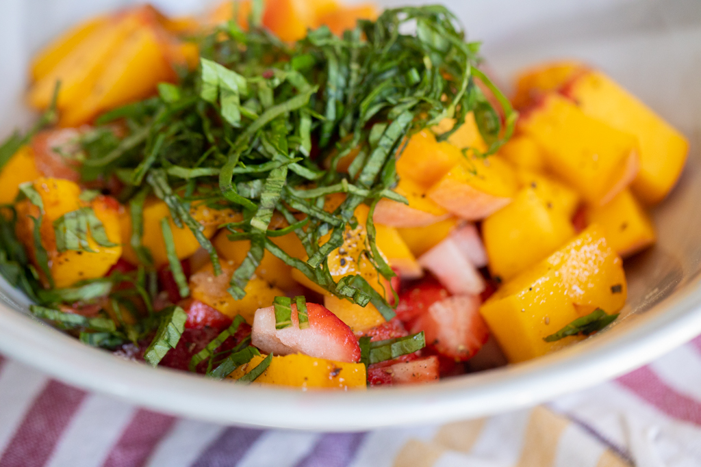 Bowl of diced peaches and strawberries topped with shredded basil.