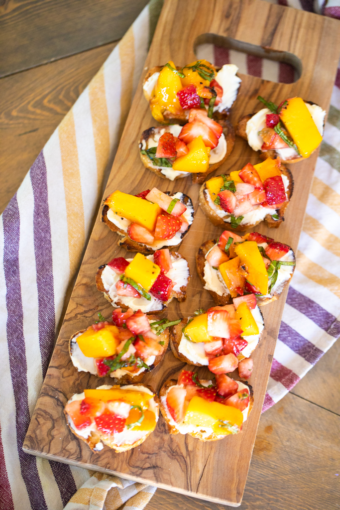 Toasted small bread rounds, topped with sweetened mascarpone and diced strawberries and peaches on a wooden serving board set on a striped dish towel.
