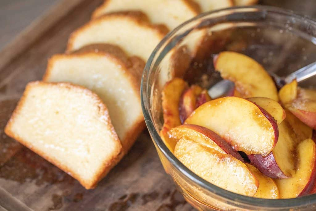 Glass bowl of sliced peaches next to a line of sliced pound cake on a wooden cutting board.