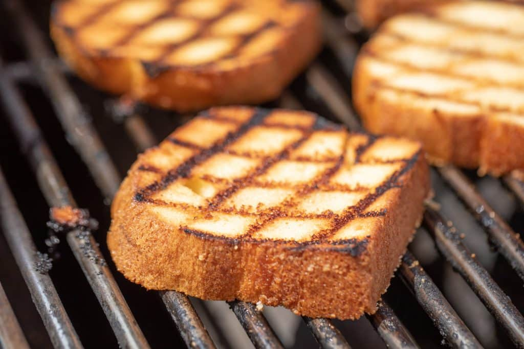 Thick slices of grilled pound cake on the grill grates of a grill.
