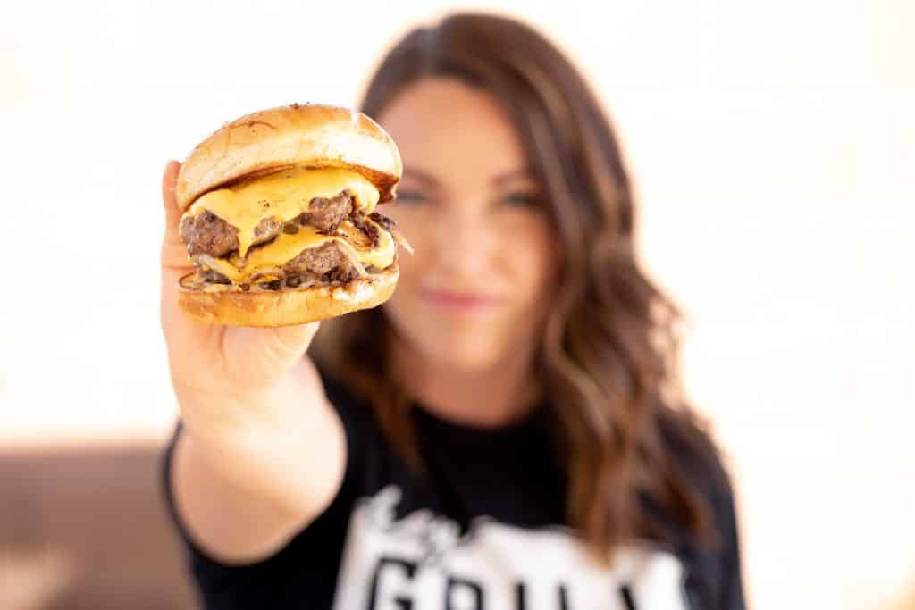 Susie Bulloch holding a double patty smashburger.