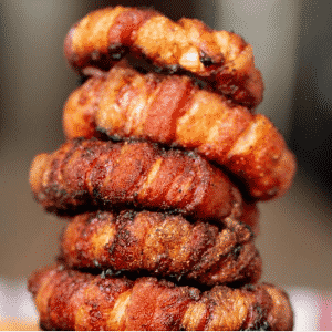 Five stacked bacon wrapped onion rings.