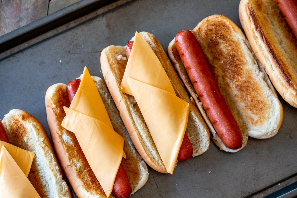 Row of smoked hot dogs on toasted hot dog buns topped with two slices of American cheese.