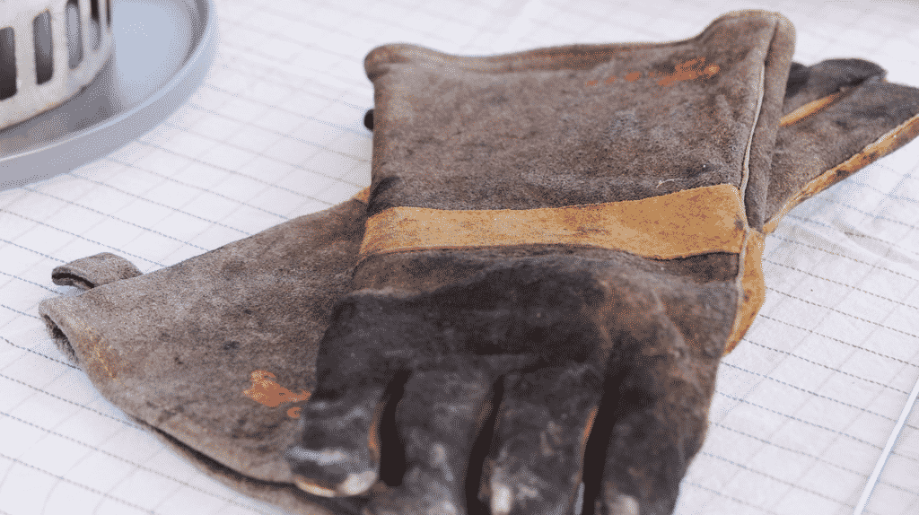 Worn leather gloves on a white tablecloth.