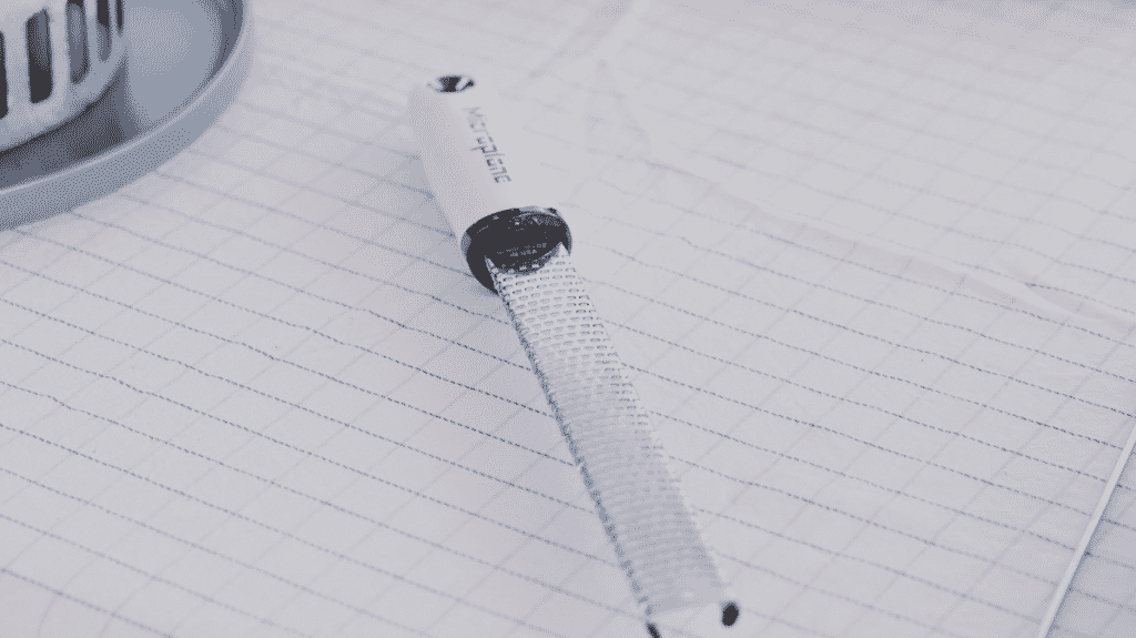 Microplane grater on a white tablecloth.