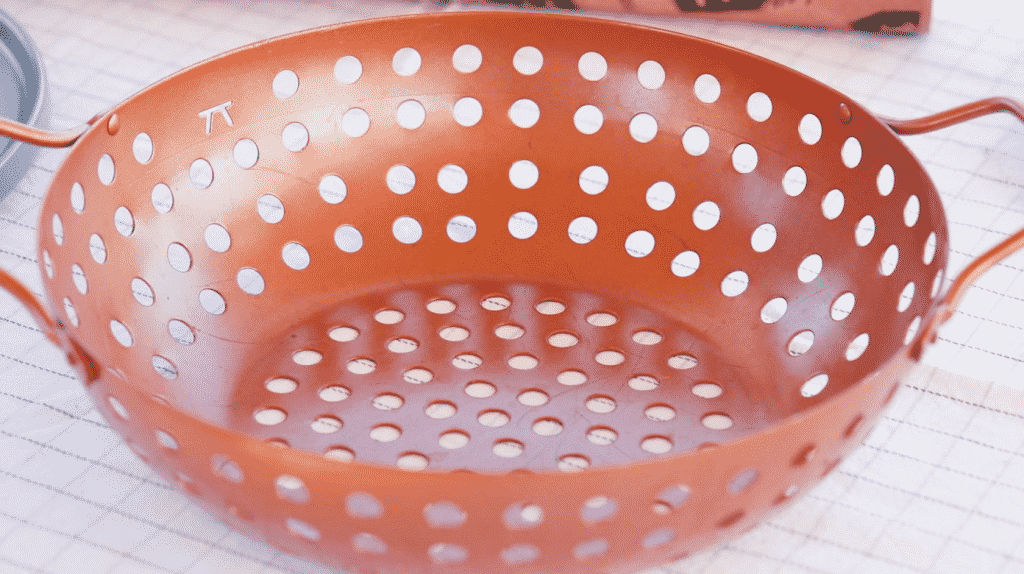 Copper grill wok on a white table.