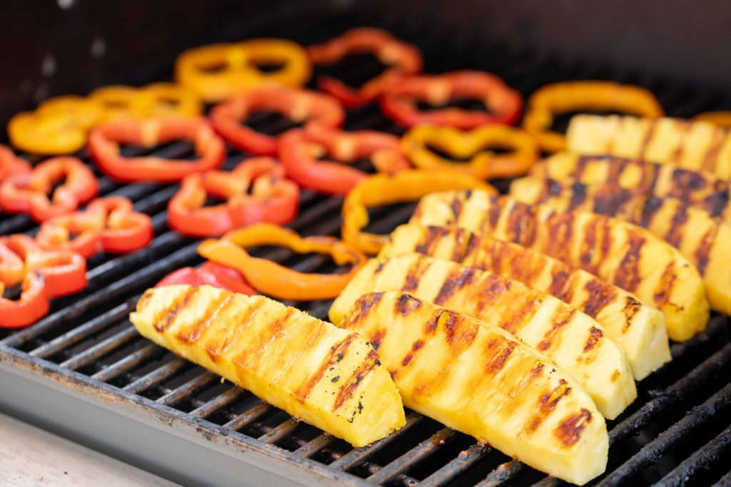 Pineapple spears and bell pepper slices on the grill grates of a grill.