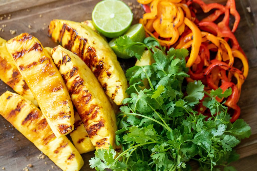 Sliced grilled pineapple and bell peppers next to lime halves and fresh cilantro on a cutting board.