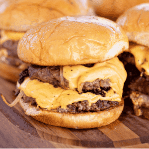 Smash burgers arranged on a wooden cutting board.