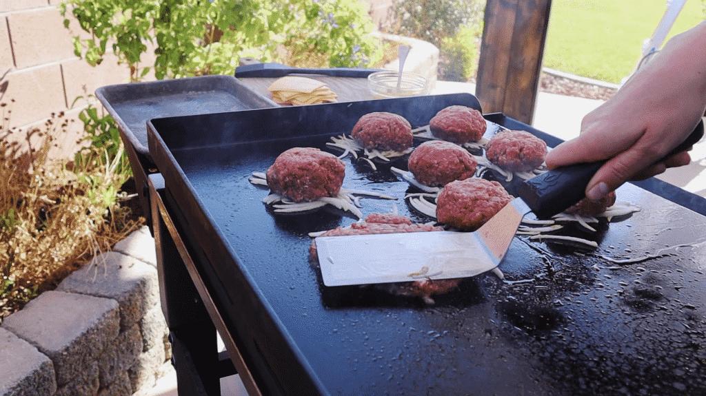 Flat spatula smashing a burger patty ball on a flat top griddle.