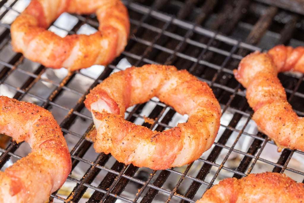 bacon wrapped onion rings on a cooling rack