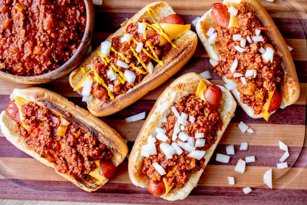 Four chili cheese hot dogs on a wooden cutting board garnished with sliced onions.
