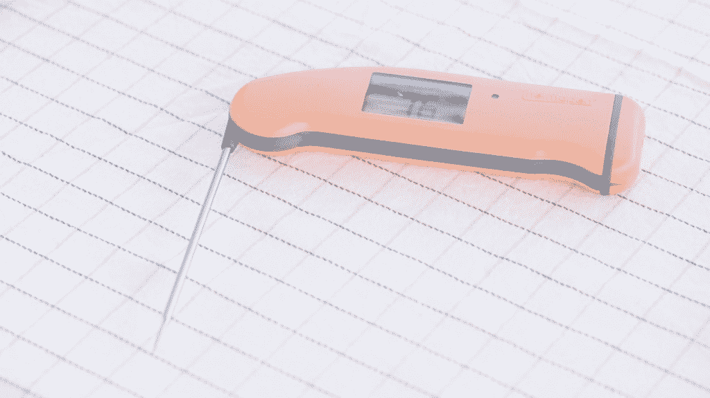 Peach ThermoWorks Thermapen Mk4 on a white tablecloth.