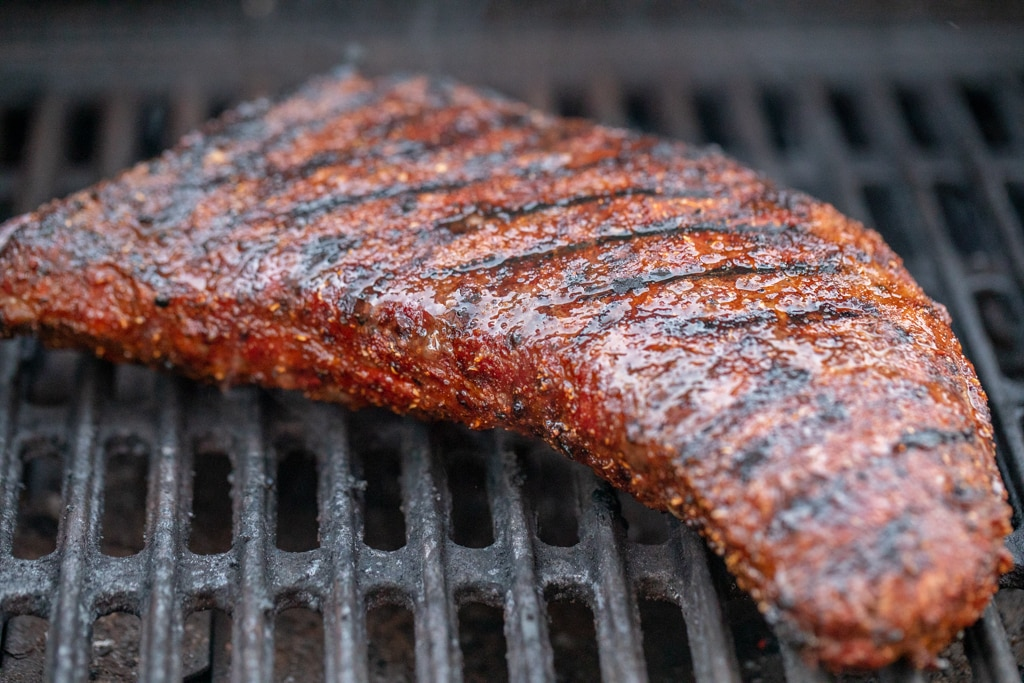 smoked coffee rub tri tip on the grill grates of a smoker.